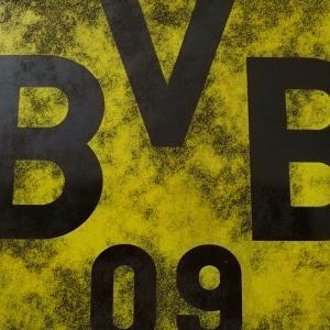 Dieses Bild von Thorsten Hülsberg zeigt einen Ausschnitt des Logos von Borussia Dortmund mit dunklen Wolken davor.