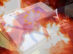 Diese Fotocollage von Thorsten Hülsberg zeigt Hände an einer EU-Torte, welche in Flammen aufgeht.