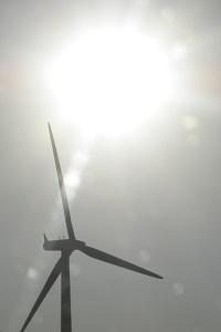 Diese Farbfotografie von Thorsten Hülsberg zeigt die Sonne und ein Windrad.