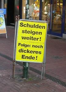Dieses Farbfoto von Thorsten Hülsberg zeigt ein gelbschwarzes Plakat, welches Schuldenfolgen erläutert.