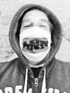 Dieses in Grautönen bearbeitete Bild von Thorsten Hülsberg ist ein Selbstportrait mit Anti-Maske.