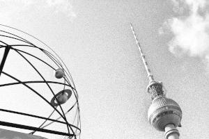 Dieses Graustufenbild von Thorsten Hülsberg zeigt die Weltzeituhr und den Fernsehturm am Alexanderplatz in Berlin-Mitte.