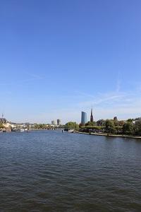 Diese Farbfotografie von Thorsten Hülsberg zeigt einen Blick über den Main in Frankfurt und das EZB-Gebäude am Horizont.