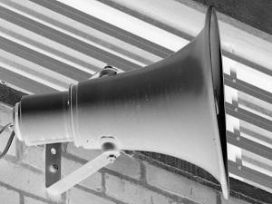 Dieses invertierte Schwarzweißfoto von Thorsten Hülsberg zeigt einen Lautsprecher der an einer Außenwand befestigt ist.