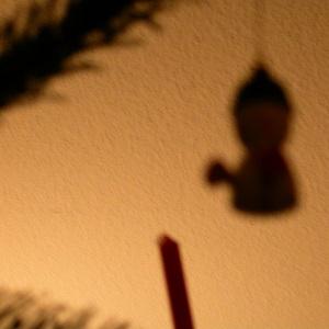 Diese Fotografie von Thorsten Hülsberg zeigt Schatten von einem Tannenbaum mit Kerze und einer Figur.
