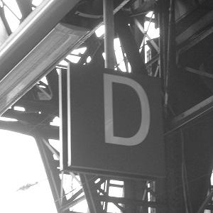 Schwarzweißfotografie des Buchstaben D zur Gleiserkennung an einem Bahnhof
