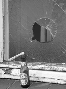 Diese Schwarzweißfotografie aus Leichlingen von Thorsten Hülsberg zeigt eine Fensterscheibe mit einem Loch, einem verrotteten Rahmen und einer leeren Flasche Bier davor.