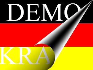 Dieses farbige Bild von Thorsten Hülsberg zeigt eine Deutschlandfahne von der sich in weißer Schrift das Wort Demokratie abrollt.