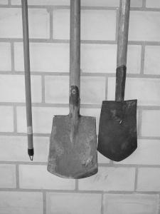Diese Schwarzweißfotografie von Thorsten Hülsberg zeigt an einer Wand aufgehangene Spaten.