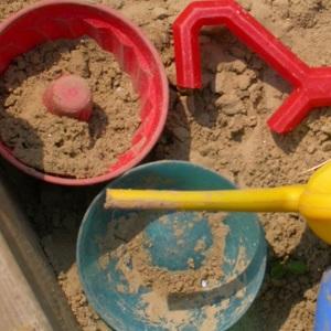 Dieses Farbfoto von Thorsten Hülsberg zeigt den Ausschnitt eines Sandkastens mit Förmchen.
