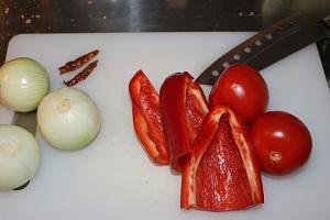 Diese Farbfotografie von Thorsten Hülsberg zeigt ein Schneidebrett mit Messer und Gemüse.