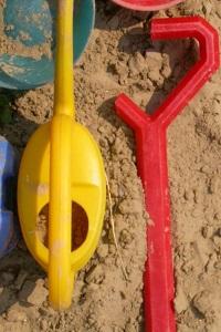 Diese Farbfotografie von Thorsten Hülsberg zeigt Kinderspielzeug in einem Sandkasten.