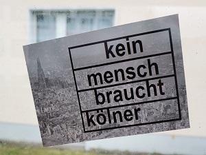 Diese Farbfotografie von Thorsten Hülsberg zeigt einen Aufkleber dessen Hintergrund Köln zeigt und darüber ist zu lesen: Kein Mensch braucht Kölner.