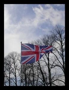 Dieses schwarzumrandete Farbfoto von Thorsten Hülsberg zeigt die britische Fahne im Wind vor einer Baumreihe ohne Blätter.