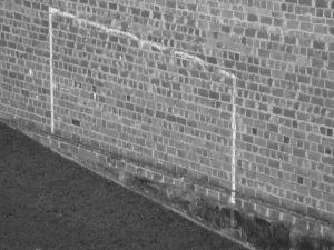 Diese Schwarzweißfotografie aus Freiburg im Breisgau von Thorsten Hülsberg zeigt ein kleines Stück Rasen und eine Backsteinmauer auf die mit Kreide ein Tor gezeichnet wurde.