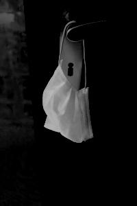 Dieses Foto von Thorsten Hülsberg zeigt künstlerisch bearbeitet eine Maske an einer Türklinke.