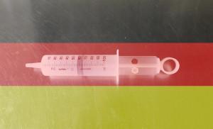 Dieses Bild von Thorsten Hülsberg zeigt eine Spritze überlagert von einer Deutschlandfahne.