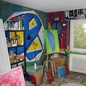 Fotografie von Thorsten Hülsberg zeigt einen Teil des Ateliers mit Werken, Wandmalerei und Arbeitsmaterialien.
