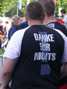 Diese Farbfotografie von Thorsten Hülsberg zeigt einen Mann von hinten auf dessen T-Shirt zu lesen ist DANKE FÜR NICHTS!
