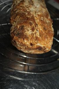 Dieses Farbfoto von Thorsten Hülsberg zeigt ein Brot auf einem Gitter auf der Küchenarbeitsplatte.