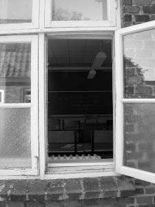 Diese Schwarzweißfotografie von Thorsten Hülsberg zeigt den Blick durch ein offenes, altes Fenster in ein Klassenzimmer.