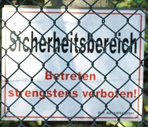 Dieses Farbfoto von Thorsten Hülsberg zeigt ein Warnschild hinter Maschendrahtzaun mit der Aufschrift Sicherheitsbereich Betreten strengstens verboten!
