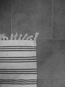 Diese Schwarzweißfotografie von Thorsten Hülsberg zeigt einen Teil eines Teppichs auf Fliesen.