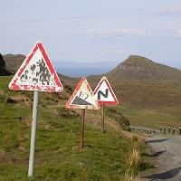 Fotografie von Thorsten Hülsberg mit verschiedenen verwitterten Warnschildern an einer Straße in den Highlands.