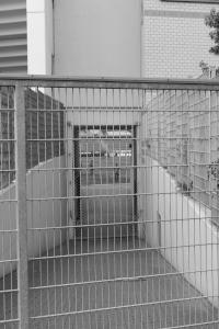 Diese Schwarzweißfotografie von Thorsten Hülsberg zeigt einen verschlossenen Zugang zur leeren BayArena in Leverkusen.