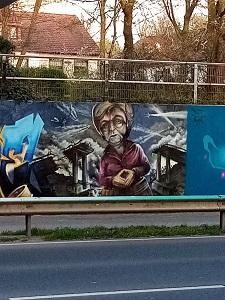 Dieses Farbfoto zeigt eine Straße und im Hintergrund ein Merkel-Graffiti und ein Haus.