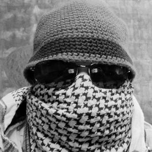 Hier sieht man ein Schwarzweißselbstportrait von einem vermummten Thorsten Hülsberg.