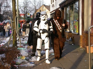 Dieses Farbfoto zeigt eine klassische Szene aus dem Straßenkarneval mit drei Figuren aus Star Wars im Vordergrund.