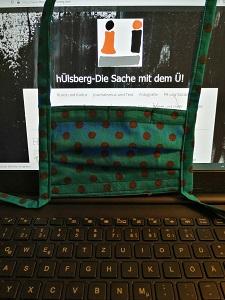 Dieses Farbfoto von Thorsten Hülsberg zeigt einen Laptop mit der Website von hÜlsberg – Die Sache dem Ü und eine davor gehangene Gesichtsmaske.
