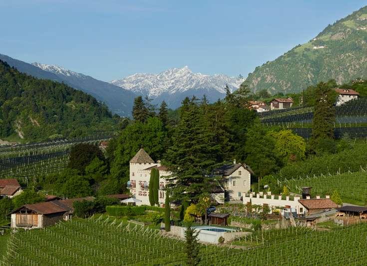 Schloss Plars eingebettet in Weinberge mit Blick auf die Südtiroler Berge
