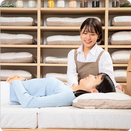 体験は無料ですのイメージ写真 オーダー枕を抱えた女性が微笑んでいる