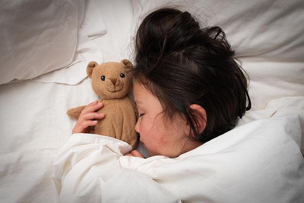 テディベアと一緒にぐっすり寝る女の子