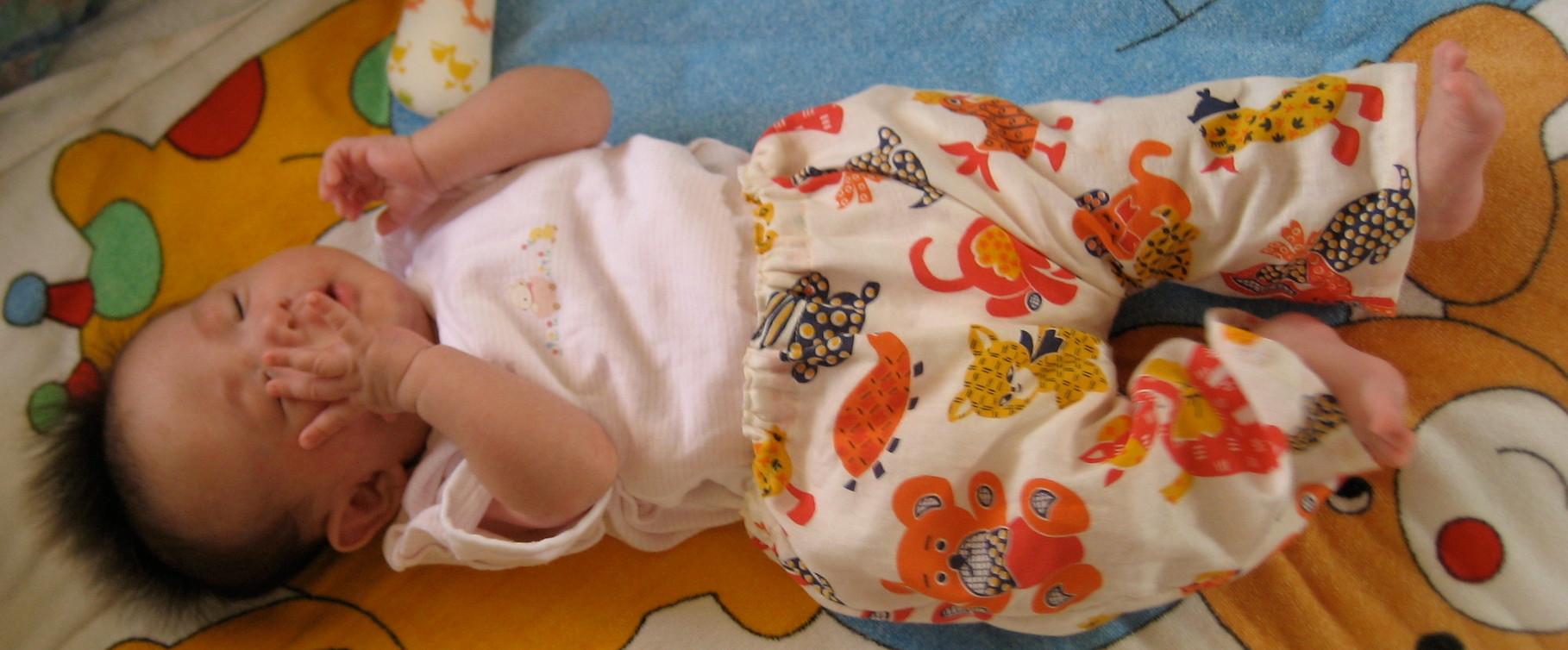 赤ちゃん用のロンパースの上に着せてます。