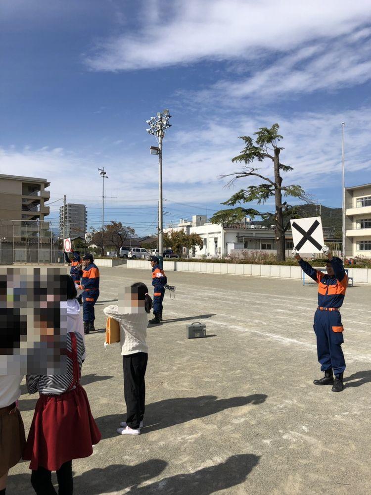 【ブログにリンク】朝日小学校の防災訓練に、消防団員として参加しました。画像は、〇✖形式で実施した「防災クイズ」。「✖」のボードを持っているのが私です=2018年10月31日