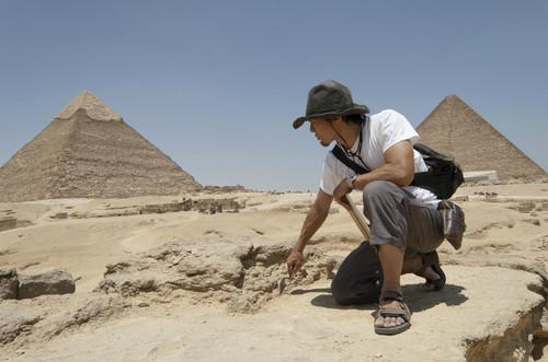 ピラミッドをバックに発掘する河江肖剰先生