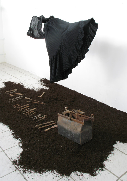 (2011, mixed media, old tools, earth, clothes, leather bag)