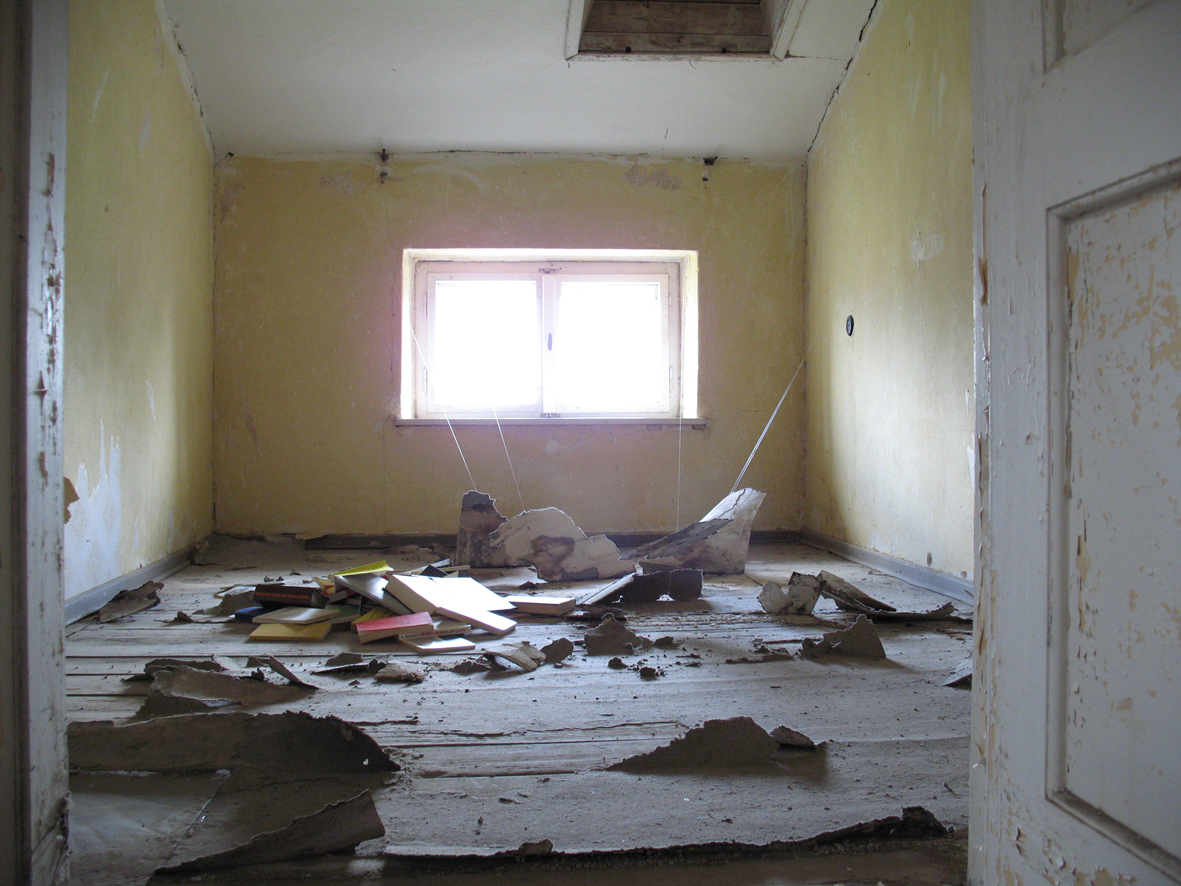 installation with remains of wall paper and carpet, obsolete history books (2007)