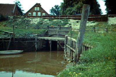 Deicharbeiten Strohausen- Oben auf der Deichkuppe laufen die Schienen für die Loren, seitlich mit Spundwänden vor Abbruch gestützt. Die letzten tage das alten Sieles von 1912 sind gezählt.(Juli 1971)