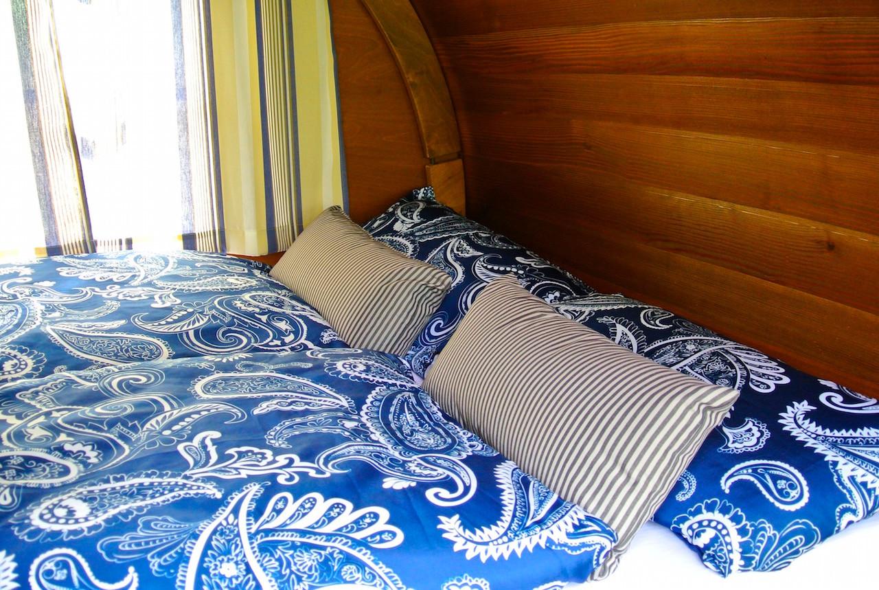 Im Fass erwarten Sie ein quer eingebautes Doppelbett mit bequemen Kaltschaummatratzen (Liegefläche 140 x 195 cm), Kissen & Decken, Fenster auf beiden Seiten, Licht, Steckdosen und Heizung