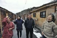 昨年末に畳が導入された「町営」仮設住宅で、住民と語らう自治会長の柳下さん(右から2人目)(7日、岩手県住田町で)