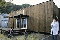 「KAMAISHIの箱」。左後方のプレハブ店舗と好対照を見せる。仮設住宅に暮らす母子連れが立ち寄った(3日、釜石市の大只越公園)