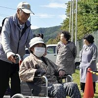 仮設住宅の防火訓練で車いすを押して避難する夫婦(2日、岩手県宮古市田老で)