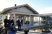 伊東豊雄氏(左から4人目)らが共同設計した「みんなの家」。右奥のプレハブ集会所と、縁側を兼ねた廊下でつなげた(10月26日、仙台市宮城野区)
