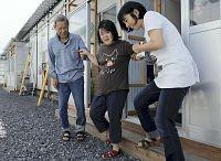 視覚障害があるため、仮設住宅の入り口で転倒する不安がある志田さん(中央)(10日、大船渡市で)