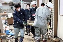 土砂に埋まった民家から協力して畳を運び出すボランティアたち=岩手県大槌町で2011年4月8日、小川昌宏撮影