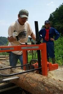 【移動式製材機を使い、流木を材木に加工する「水守の郷・七ケ宿」の海藤理事長(右)ら=石巻市北上町相川】